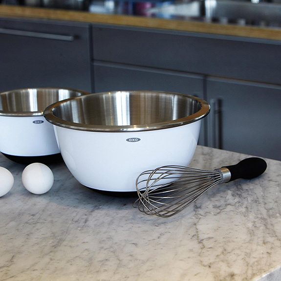 Black-handled balloon whisk beside two bowls on a metal counter