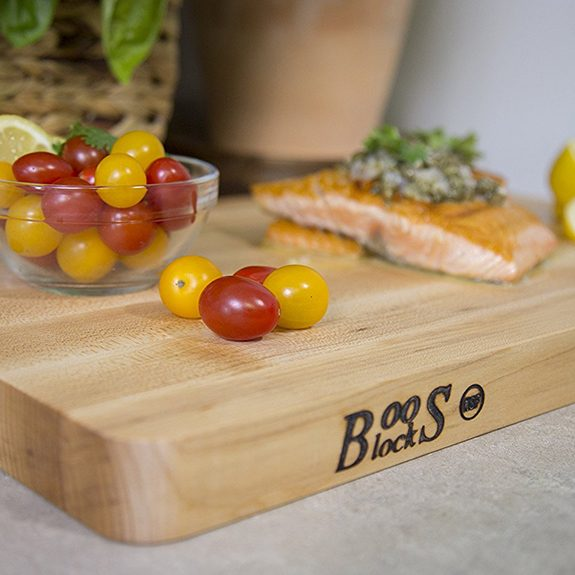 Thick, wooden cutting board with the word 'Boos Block' burned into the left corner and cherry tomatoes in a glass bowl and salmon resting on top of it