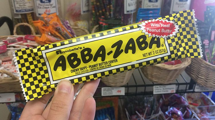 Hand holding up a classic yellow Abba-Zabba bar