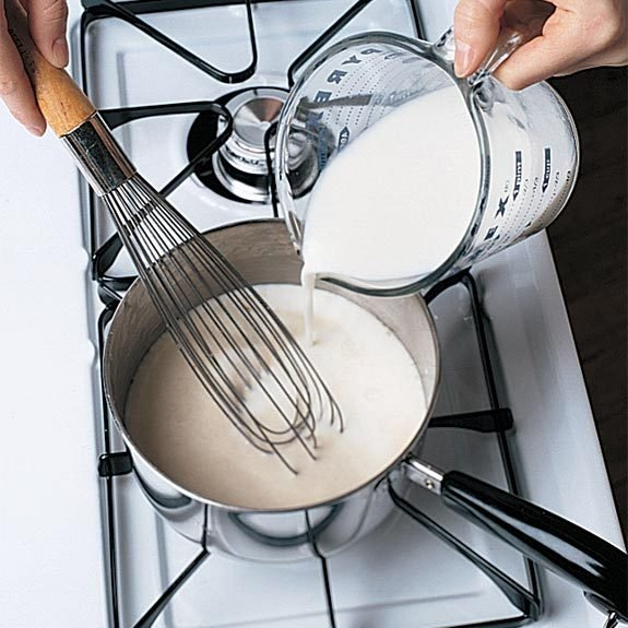 Adding milk to make béchamel sauce for baked macaroni and cheese