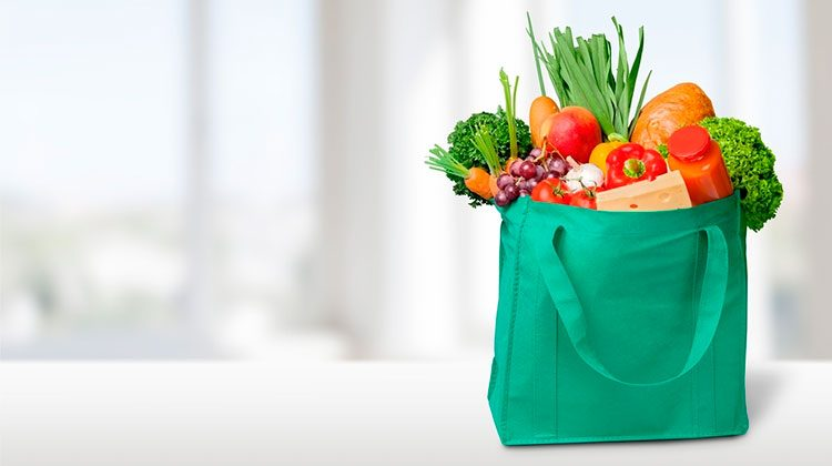green tote bag filled with different produce and nearly overflowing