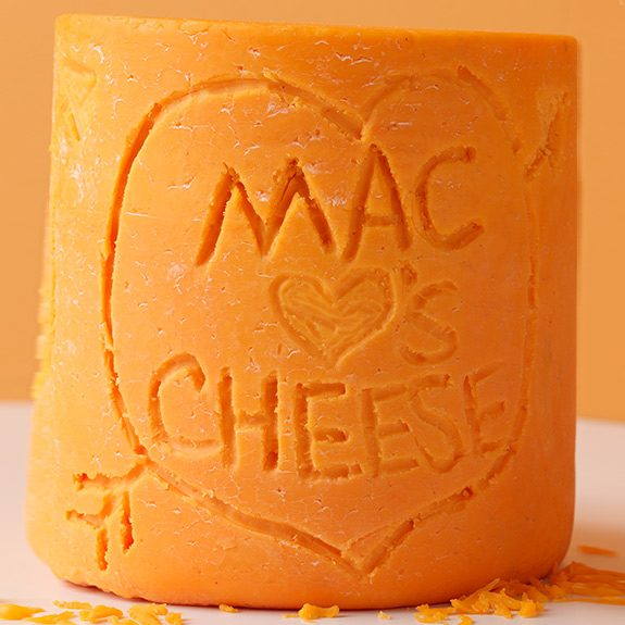Block of cheddar cheese with Mac Hearts Cheesecarved into it