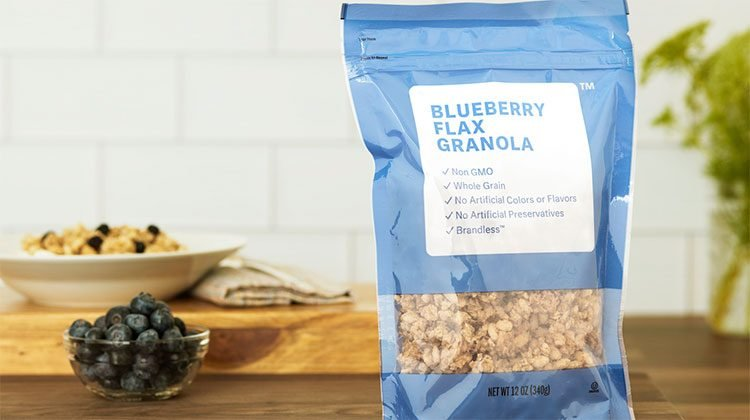 Blue bag with blueberry flax granola on a wooden table with a cup of blueberries nearby and a bowl of the granola beyond that