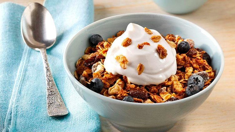 granola piled high in a light blue bowl mixed with blueberries and with whipped cream on top
