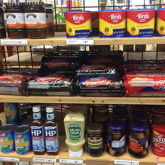 Wooden shelves filled with British staples including cookies, condiments, jam and more