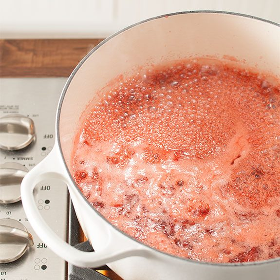 Strawberry jam mixture bubbling in a Dutch oven on the stovetop