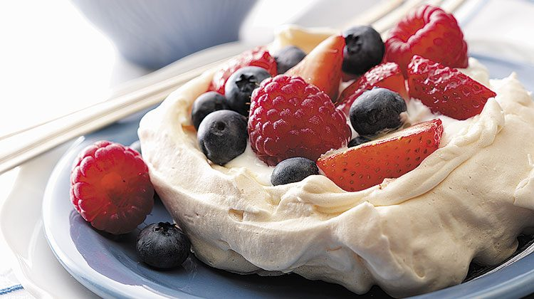 Meringue cup filled with blueberries, strawberries, raspberries and custard