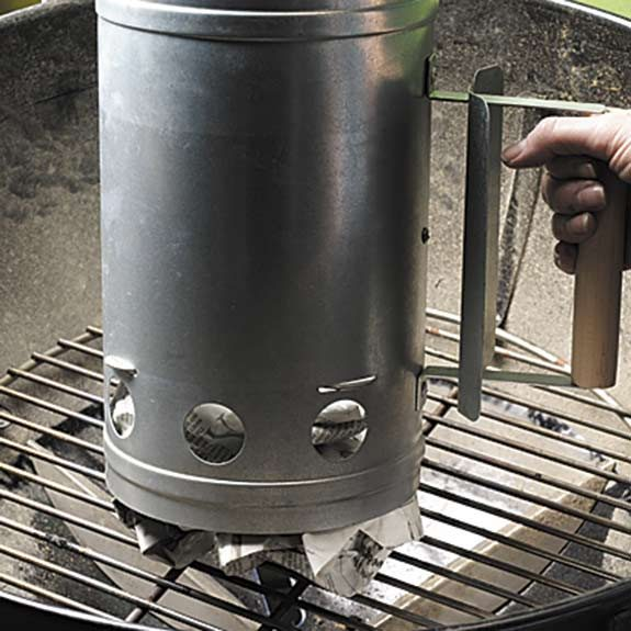 Using newspaper to light a charcoal grill with a chimney starter