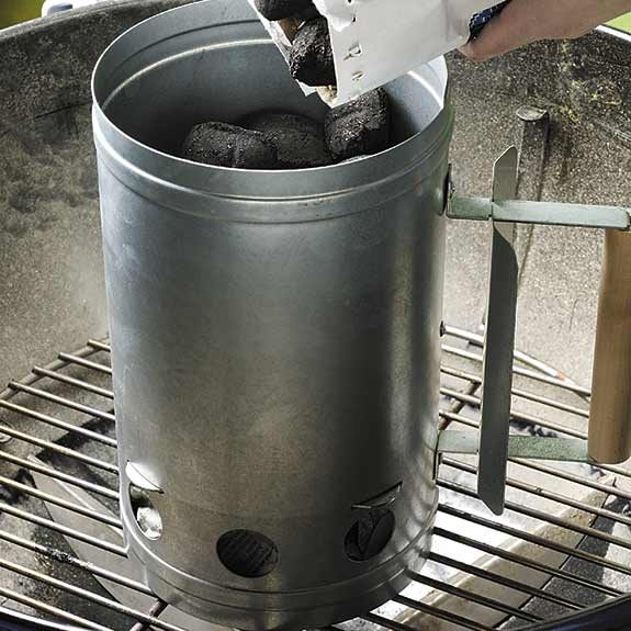 Adding briquettes to a chimney starter to light a charcoal grill.