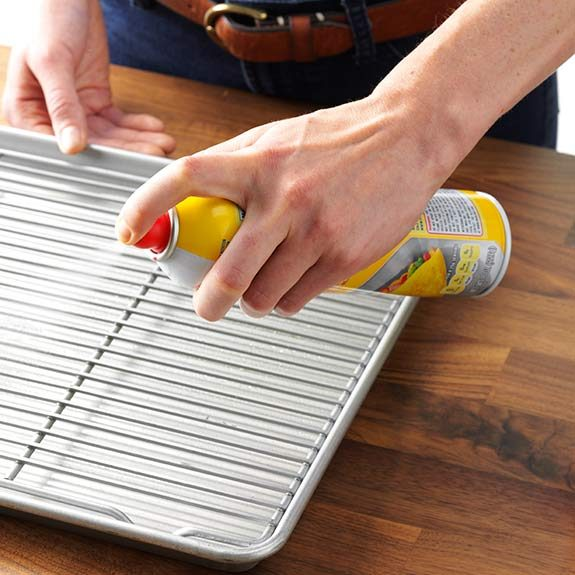 Coating a wire rack over a baking pan with cooking spray.