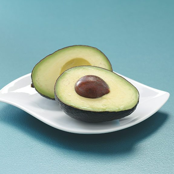 Ripe and bright green avocado halved with seed.