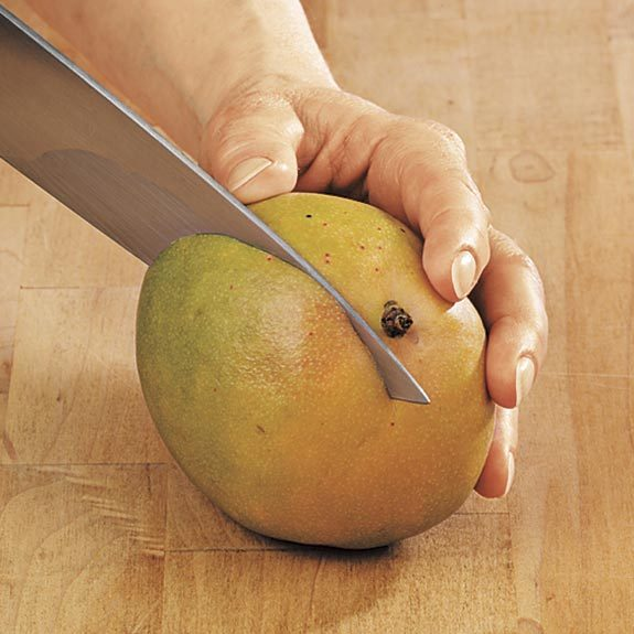 Cutting a mango lengthwise along the flat seed to remove each side of the fruit.