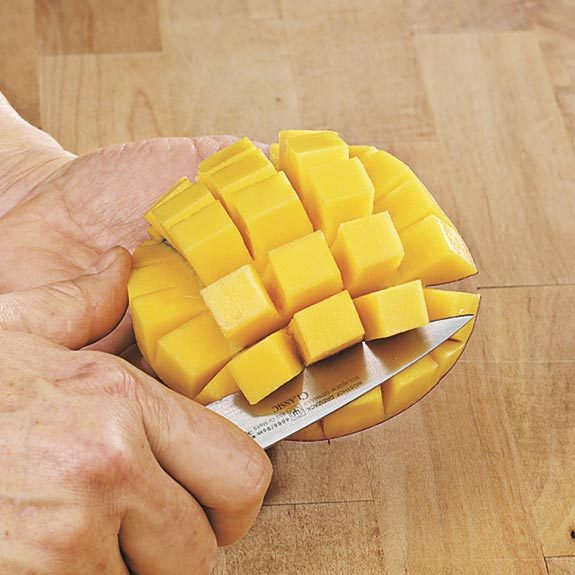 Pushing mango skin up to turn the scored fruit out while cutting fruit from skin.