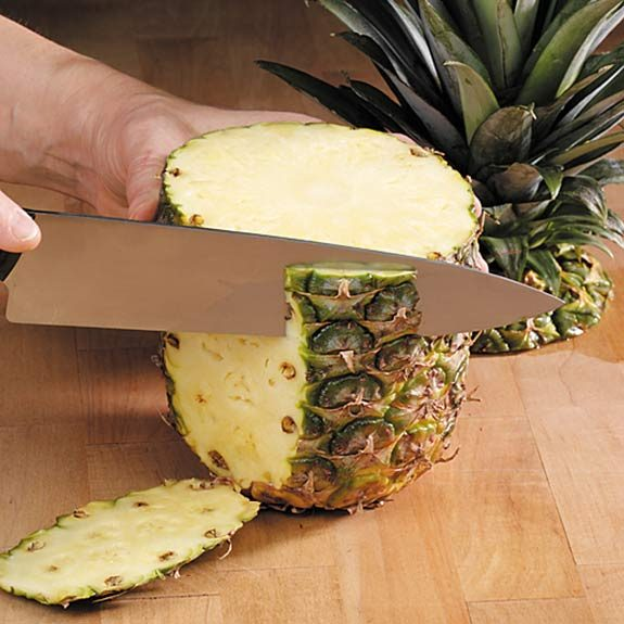 "Alt=""Cutting a pineapple from the crown to the base."""