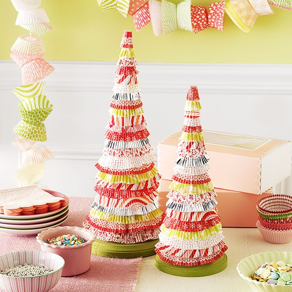 Two tree decorations dominate a green, pink and white table display. Both are constructed from layers of cupcake liners with different patterns and slightly different colors