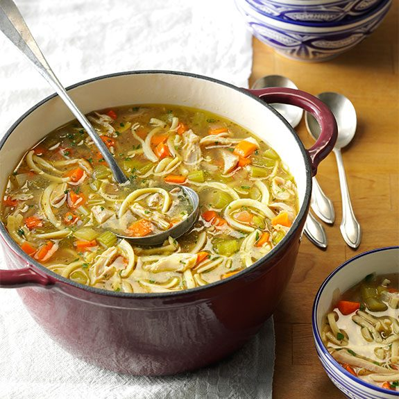 A Dutch oven filled with fresh homemade chicken noodle soup
