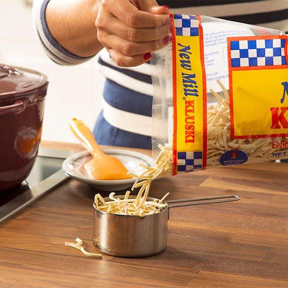 Measuring kluski egg noodles for a chicken noodle soup recipe
