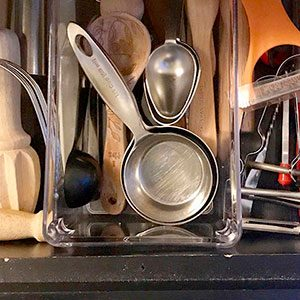 Kitchen utensil drawer with clear bins being used to separate the tools into sections