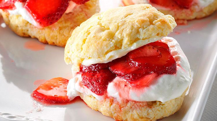 Three strawberry lemon shortcakes sitting on a platter and overflowing with strawberries