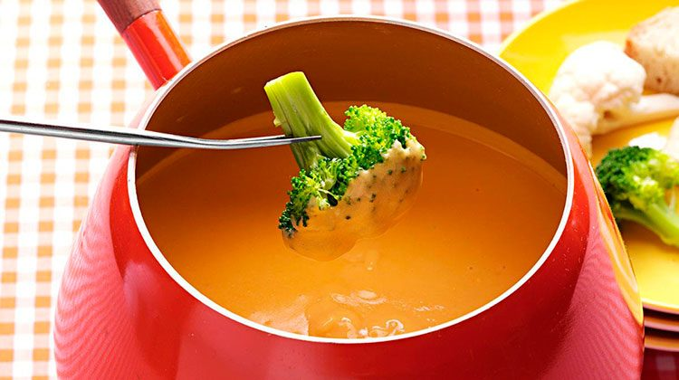 Person dipping broccoli into a red pot of cheese fondue