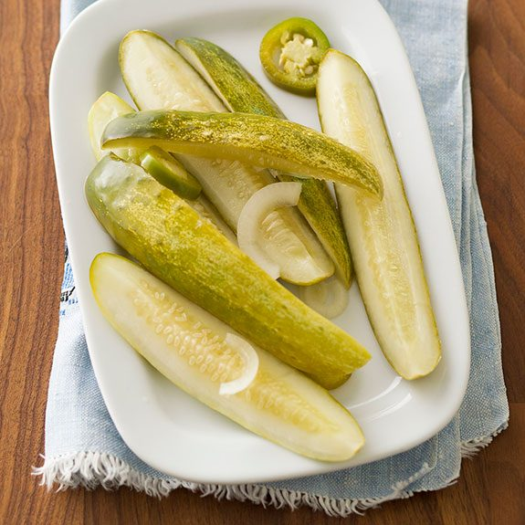 Sliced pickles in a pile on a white plate with a blue towel below on a wooden table