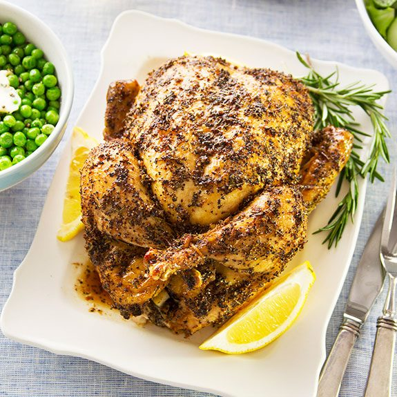Roasted chicken, covered in seasoning, sitting on a plate with lemon wedges and rosemary