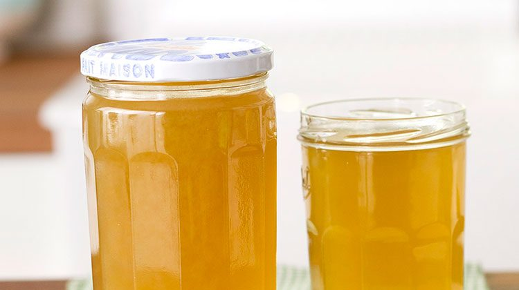 Two glass jars of vegetable broth side-by-side, one with a lid and one without