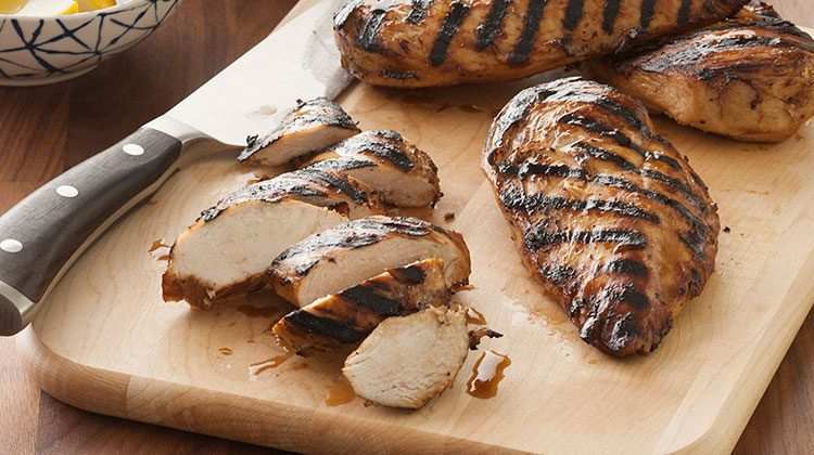 Several grilled chicken breasts on a wooden cutting board. One of the breasts has already been cut into slices and the knife is resting nearby