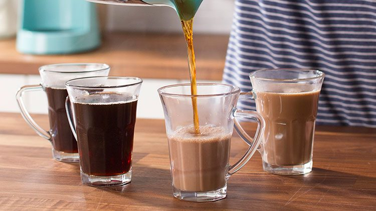 Person pouring coffee from a coffee pot into four glass cups