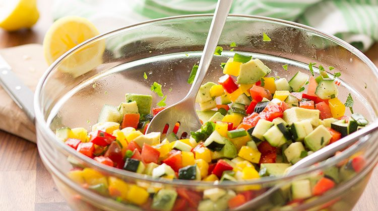 Chop salad made up of cubed cucumbers, tomatoes, avocado and peppers sitting in a glass bowl with two serving spoons