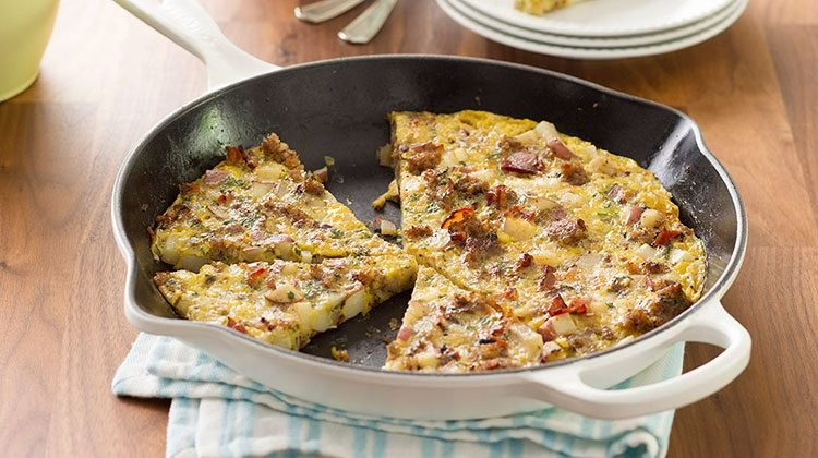 Frittata in a skillet sliced with pieces missing