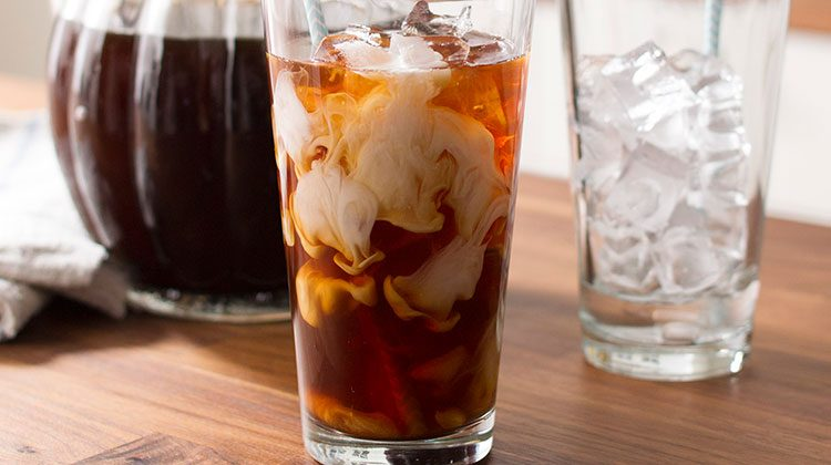 A tall glass of cold-brewed coffee with cream being swirled in
