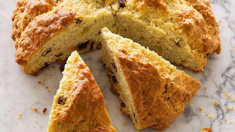 Loaf of Irish soda bread with several wedge cuts from it sitting pulled apart from the circle