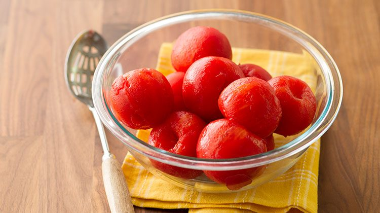 Glass bowl filled with perfectly peeled tomatoes resting on a yellow towel