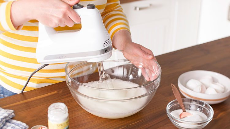 Person beating the egg whites together in a large glass bowl until they are foamy