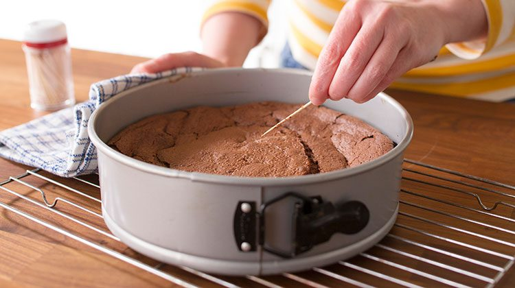 Baked flourless chocolate cake in its baking dish about to undergo the toothpick test from a person in a yellow striped shirt