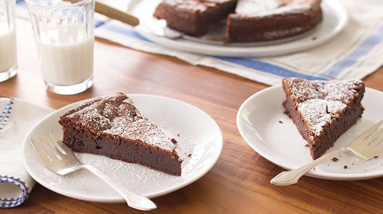 Two slices of flourless chocolate cake on separate white plates in front of the rest of the cake