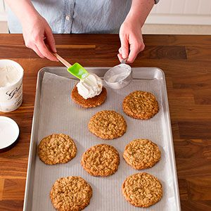 Cookies on a baking sheet with one upturned and having ice cream dumped on it gracefully with a spatula from a metal measuring cup