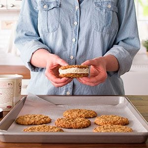 One sandwich in hand being held over the baking sheet with the un-touched cookies