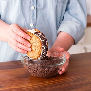 An assembled ice cream sandwich is being rolled sideways into a bowl of chocolate chips