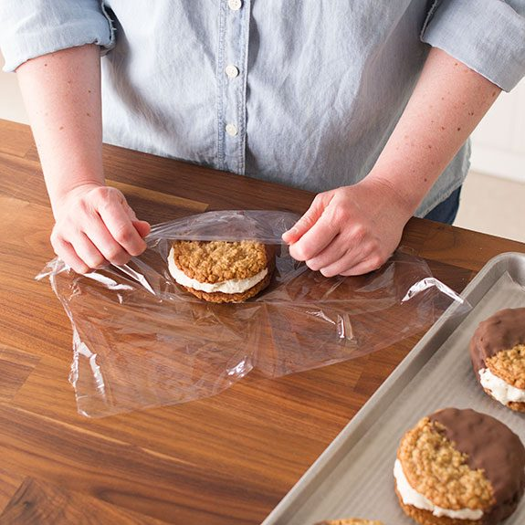 Completed ice cream sandwiches being covered with plastic wrap to eat at a later date