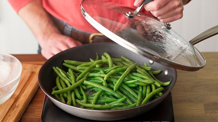 Green beans in a skillet on the stove top. A person is picking up the glass lid to show them cooking