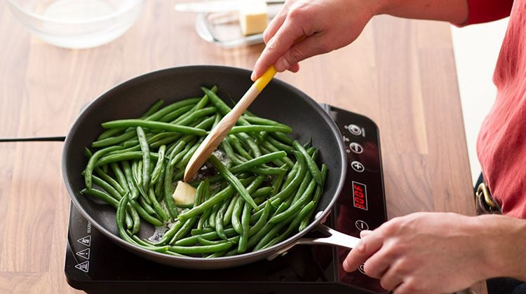 Person stirring a slice of butter into their green beans as they cook in a skillet