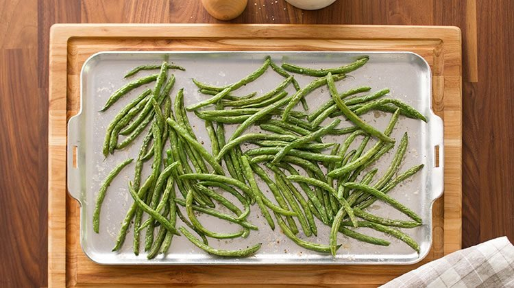 Green beans spread out over a baking sheet resting on a wooden cutting board with a gray checkered towel on its lower right corner