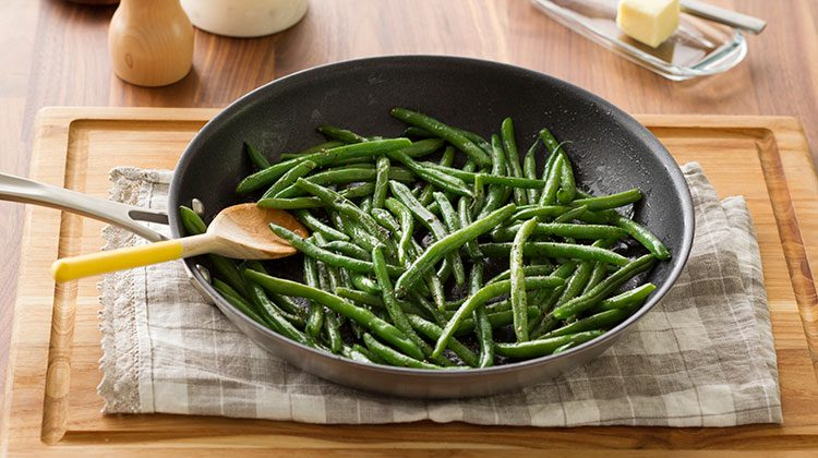 Cooked green beans in a skillet resting on top a gray checkered towel on top a wooden board