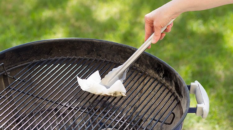 Person rubbing paper towel on their grill with metal tongs