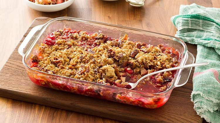 Fruit crisp in a 13x9 glass pan on a wooden cutting board on top a wooden tabletop