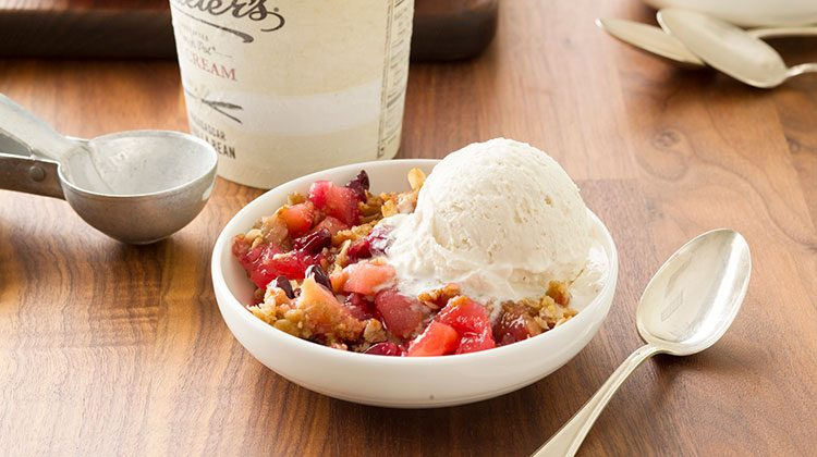 Fruit crisp beside a generous scoop of vanilla ice cream in a white bowl with a spoon ready at its side