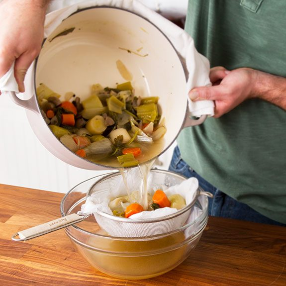Person pouring the broth from the stock pot into a colander lined with cheesecloth to catch the vegetables
