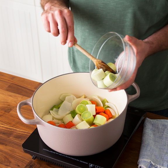 Person pushing sliced vegetables out of a glass bowl with a wooden spoon and into a stock pot on a small stovetop